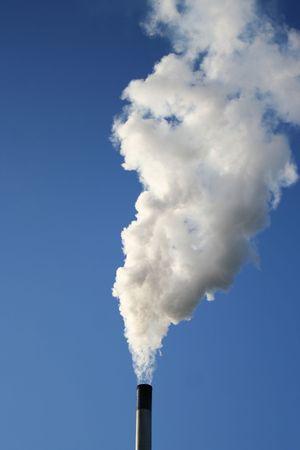 chimney billowing white smoke into blue sky