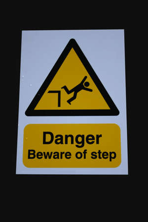 tripping: Beware of step sign isolated on black Stock Photo