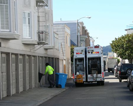 garbage truck and man collecting trash Stock Photo