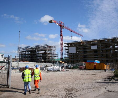 construction safety: construction workers walking near building site with crane