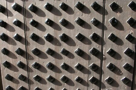 studs: wooden door with metal studs background  Stock Photo