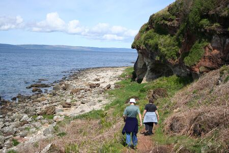 Couple walking towards kings cave west coast of Arran  Stock Photo