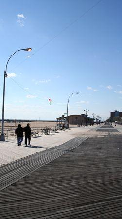 coney: couple walking along Coney Island boardwalk Brooklyn New York