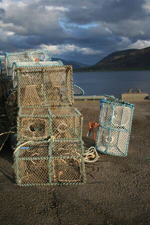 lobster pot: lobster pots stacked in piles beside sea shore
