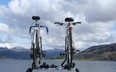 mounted: twee fietsen gemonteerd op het dak van de auto tegen de hemel