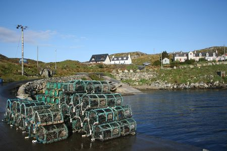 lobster pots stacked in piles beside sea shore photo
