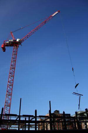 girders: Crane lifting steel girders at building site Stock Photo