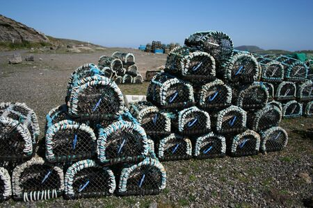 lobster pot: Piles of lobster pots stacked in groups near shore Stock Photo