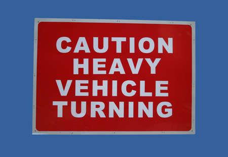 caution heavy vehicles turning sign on blue Banco de Imagens