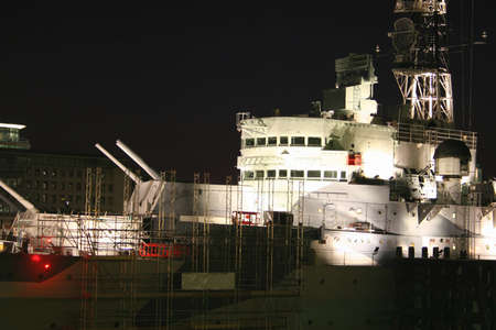 floodlit: HMS Belfast on the River Thames at night illuminated Stock Photo
