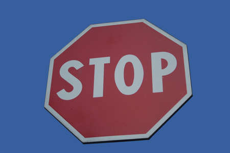 red octagonal stop sign isolated on blue Stock Photo - 1772154