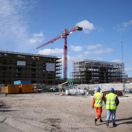 construction workers walking near building site with crane photo