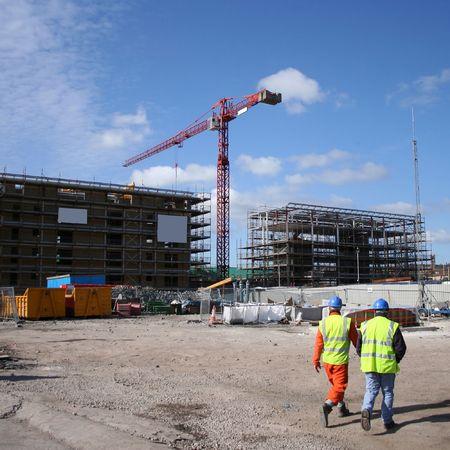 the job site: lavoratori edili a piedi vicino cantiere con gru
