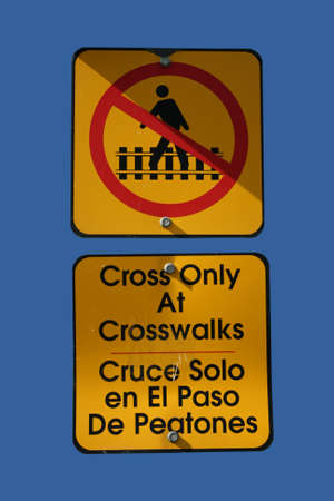bilingual: bilingual cross only at crosswalks sign against blue sky
