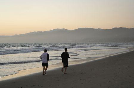 two men jogging on beach at Santa Monica at dusk  photo