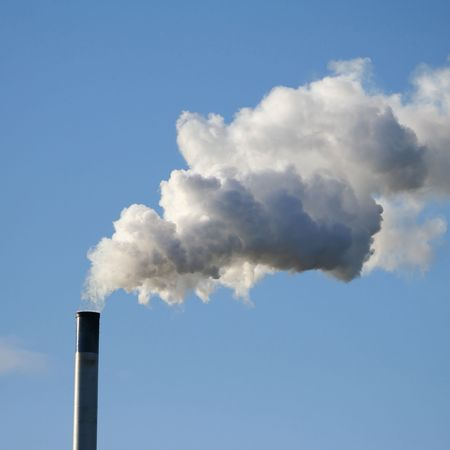billowing: chimney billowing white smoke into blue sky