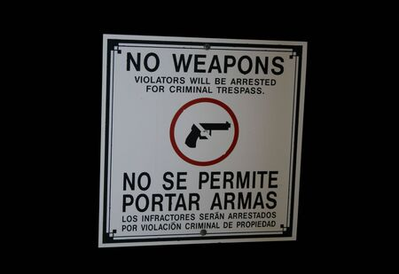Bilingual no weapons sign in English and Spanish photo
