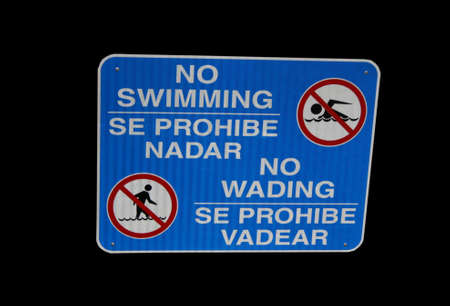 bilingual: Bilingual no swimming or wading sign in English and Spanish