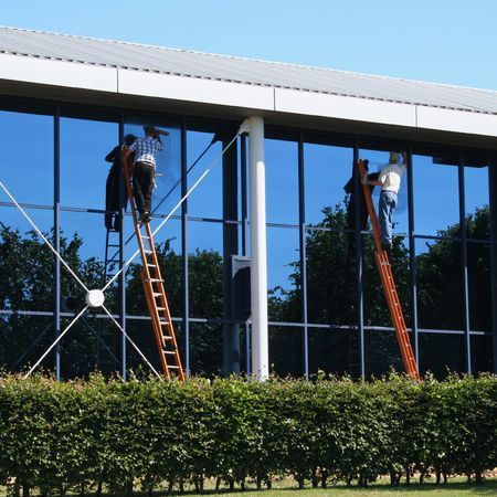 window washer: Window washers on ladders cleaning office building
