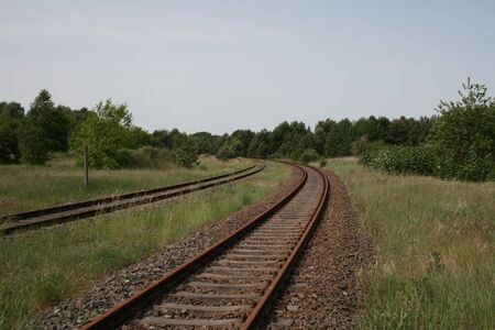 forest railroad: curve in railway track in rural area
