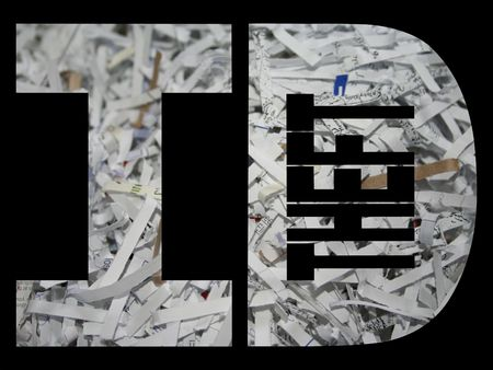 id theft: ID theft text with shredded paper background