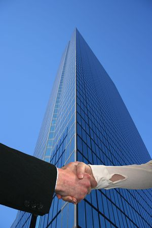 handshake with tall skyscraper and blue sky Stock Photo - 3614847