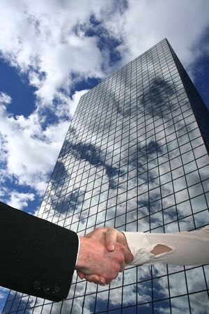 handshake with skyscraper reflecting clouds