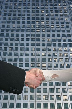 business people shaking hands with skyscraper windows photo
