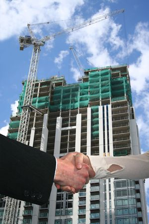 handshake between business people with construction site photo