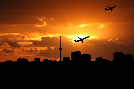 departing: planes departing with Berlin skyline at sunset Stock Photo