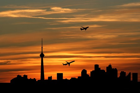 departing: planes departing with Toronto skyline at sunset
