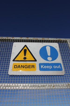 Danger keep out signs on metal fence with blue sky Stock Photo - 4196037