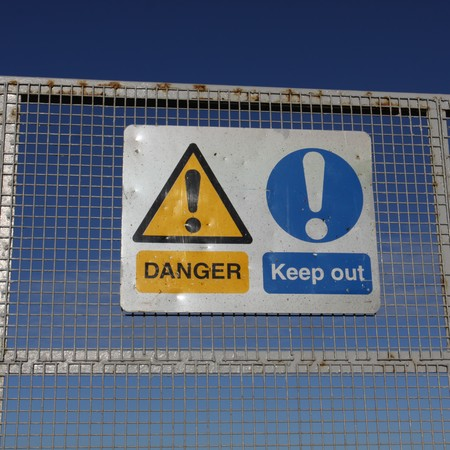 Danger keep out signs on metal fence with blue sky Stock Photo - 4206132