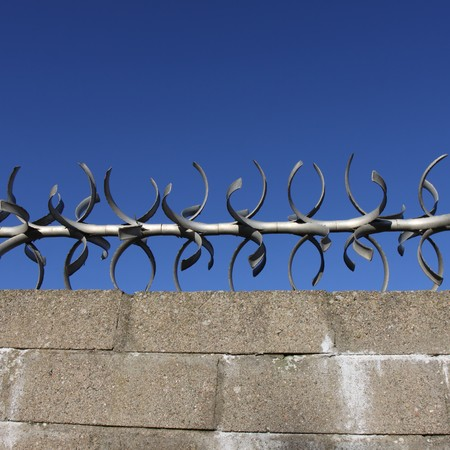 obstruct: concrete block wall with metal spikes
