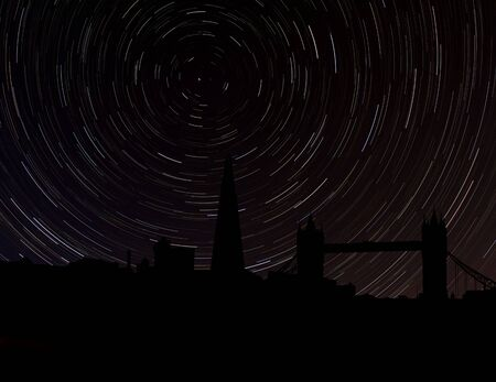 stargazing: London skyline silhouette with star trails illustration Stock Photo
