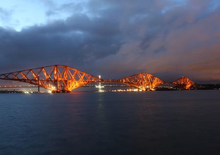 illuminated: Forth Rail Bridge illuminated at dusk Scotland Stock Photo