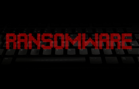 Ransomware pixellated red text over black keyboard illustration