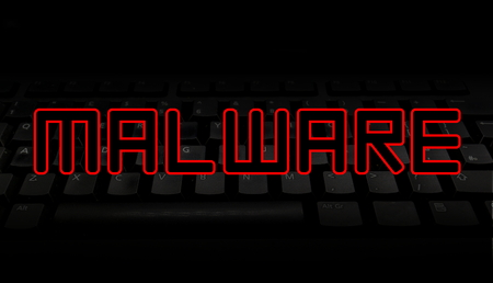 Malware red text over black keyboard illustration