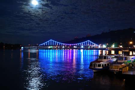 dnipro: Pedestrian bridge The Park Bridge and multicoloured Dnipro at night