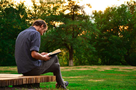 man holding book: Guy sitting on a bench in the park reading book Stock Photo