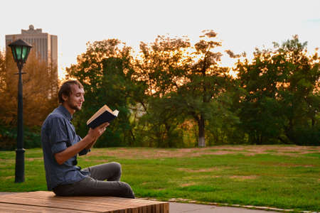 happy teenagers: Guy sitting on a bench in the park reading book Stock Photo
