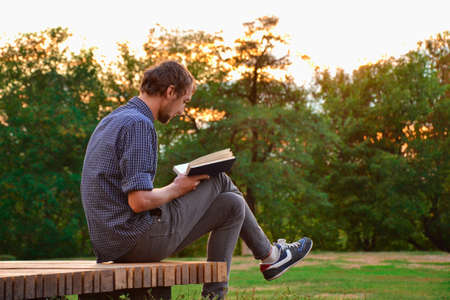 Guy sitting on a bench in the park reading book Stockfoto