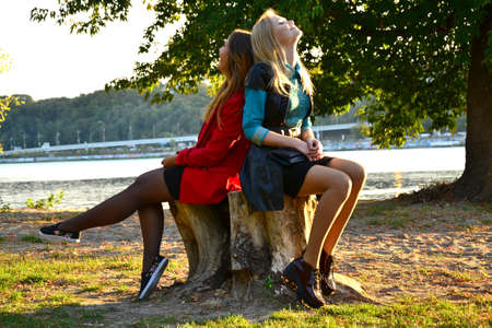 two girls: Two girls sitting back to back outdoors Stock Photo