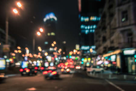 Blurred glowing skyscrapers and cars. Night city street  lights background