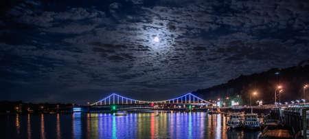 Glowing multicoloured city bridge above river at night Stock Photo