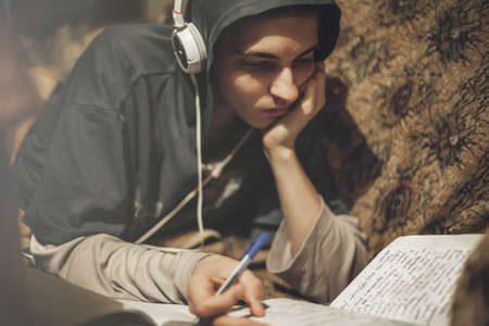 Teenage student guy studying lying on the sofa at home listening to music Stock Photo