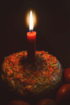 easter candle is burning: Easter cake with candle and painted eggs in the dark
