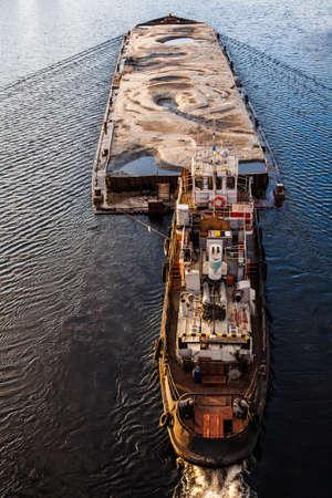 Tugboat pushing barge with sand
