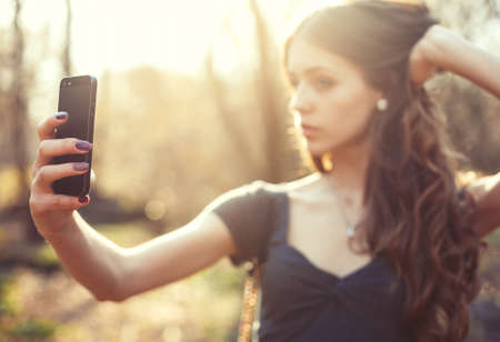 making dresses: Girl making selfie photo on smartphone in the park. Focus on phone Stock Photo
