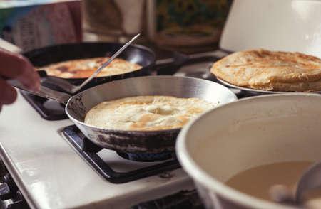 old gas stove: Grandmother making pancakes